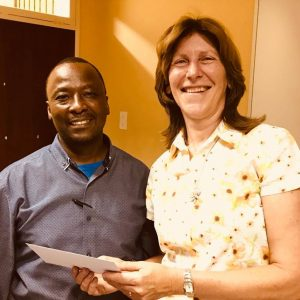 Senior Administrative Clerk in VISPOL - Lawrence Kale - is given a voucher of appreciation from the CPF for helping save an elderly person from a burning house.