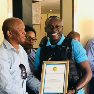 Constable Mashaba receives a certificate of appreciation from Station Commander Colonel Gopane