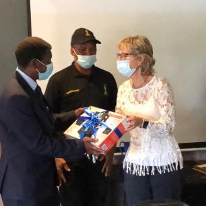 Fran Haslam, chairperson of the Zoo Lake User Group hands Colonel Ledwaba a gift of a DVD player and dongle to cast movies onto his TV screen.